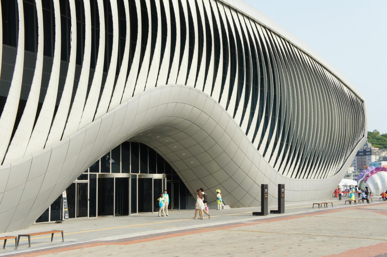 """Kuva1: Paratiisikukan terälehdillä on kyky taipua loputtomasti ilman liitoskohtia tai saranoita. Samaa ominaisuutta voidaan soveltaa rakennusten lasiseinien varjostuksessa, kuten kuvassa One Ocean -paviljongissa . Rakennus saadaan Thomas Speckin sanojen mukaan """"hengittämään valoa"""" ilman jatkuvaa ylläpitoa. Kuva: archdaily.com"""